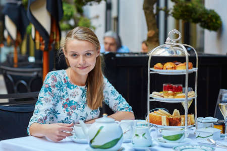 english food: Beautiful young woman enjoying afternoon tea with selection of fancy cakes and sandwiches in a luxury Parisian restaurant