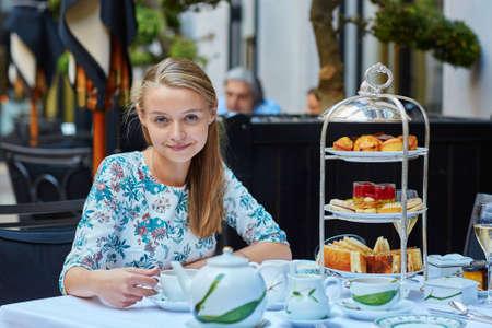 comida inglesa: Joven y bella mujer disfrutando de té de la tarde con una selección de pasteles de fantasía y sándwiches en un restaurante de lujo parisina