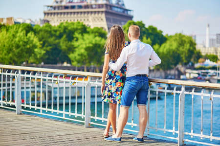 romantic couple: Young romantic couple having a date near the Eiffel tower on a bridge over the Seine in Paris, France