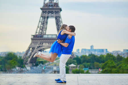 romantic hug: Romantic dating couple on Trocadero viewpoint in Paris, man is rotating his hugged girlfriend around, Eiffel tower is in the background Stock Photo