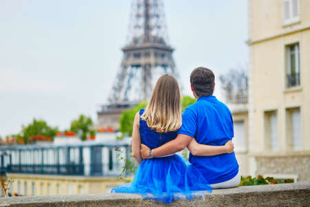 romantic hug: Romantic dating couple sitting on the parapet, hugging tenderly and looking at the Eiffel tower and Parisian roofs