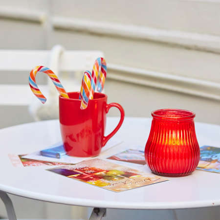 seasonal greetings: Closeup of burning candle, red mug with Christmas candy canes and colorful postcards on the table. Seasonal greetings or New Year resolutions concept