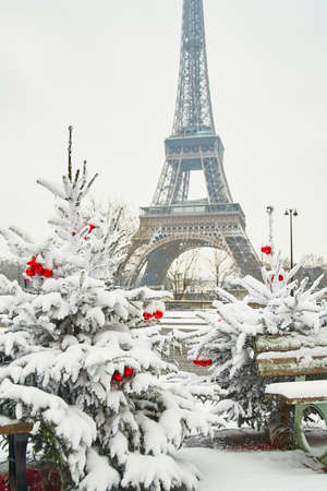 paris: Christmas tree decorated with red balls and covered with snow on a rare snowy day in Paris. Eiffel tower is in the background Stock Photo