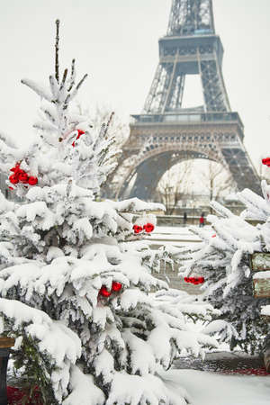 Christmas tree decorated with red balls and covered with snow on a rare snowy day in Paris. Eiffel tower is in the background Banque d'images