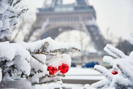 tree vertical: Christmas tree decorated with red balls and covered with snow on a rare snowy day in Paris. Eiffel tower is in the background Stock Photo