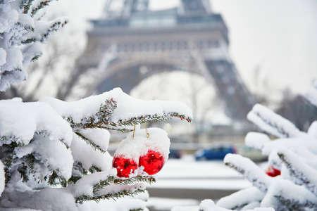 Kerstboom versierd met rode ballen en bedekt met sneeuw op een zeldzame sneeuwdag in Parijs. Eiffel toren is op de achtergrond Stockfoto