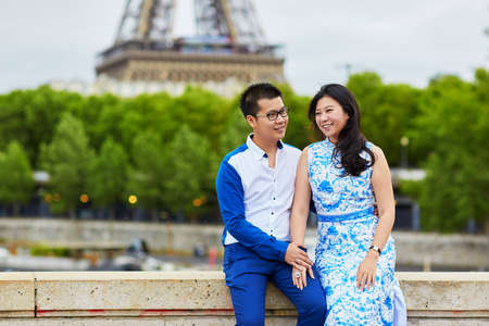 ponte giapponese: Young romantic Asian couple having a date on the bridge over the Seine near the Eiffel Tower, Paris, France