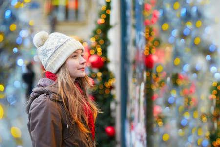 Meisje op een Parijse straat of op de markt van Kerstmis kijken naar etalages ingericht voor de kerst Stockfoto