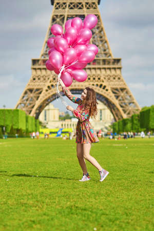 pink balloons: Happy young girl in colorful dress with huge bunch of pink balloons near the Eiffel tower in Paris Stock Photo