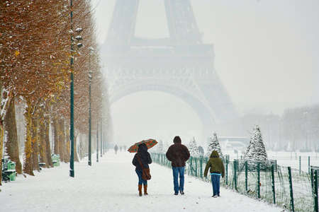 champ: Rare snowy day in Paris. Misty Eiffel Tower, Champ de Mars and lots of snow, tourists walking under the snow Stock Photo