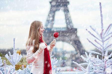 白い雪に覆われたクリスマス ツリー付近の降雪時のパリのクリスマス マーケットのカラメルりんごとバック グラウンドでエッフェル塔の少女