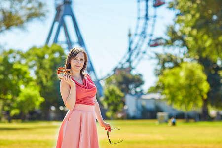 prater: Beautiful young tourist in Prater amusement park of in Vienna, Austria, holding pretzel
