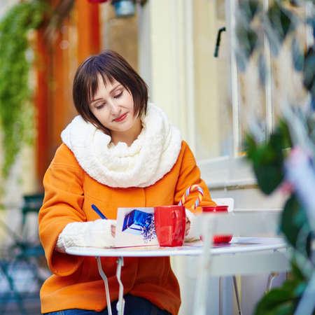 persona escribiendo: Chica joven alegre escribir tarjetas de Navidad o resoluciones de Año Nuevo en el café al aire libre de París