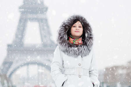 fur hood: Beautiful girl in fur hood with the Eiffel tower in background