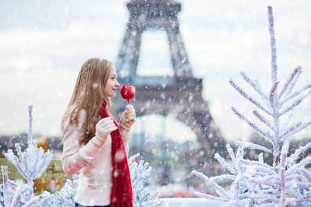 Girl with caramel apple on a Parisian Christmas market  during snowfall near white snowy Christmas trees and with the Eiffel tower in the background