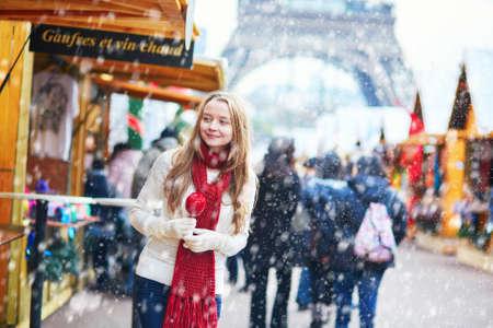 降雪の中にバック グラウンドでエッフェル塔とパリのクリスマス マーケットのカラメルりんごと幸せな若い女の子