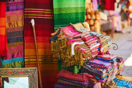 blue carpet: Colorful fabrics and carpets for sale on a street in Medina of Chefchaouen, Morocco, small town in northwest Morocco known for its blue buildings