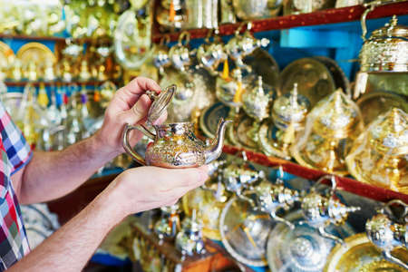 fes: European tourist selecting a traditional teapot on Moroccan market (souk) in Fes, Morocco