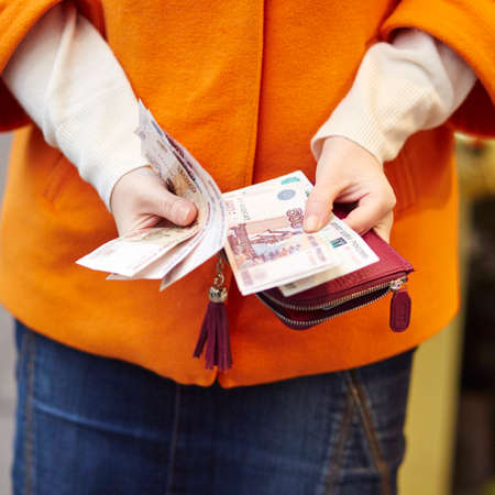 poorness: Woman hands holding purse with Russian roubles, financial crisis in Russia concept