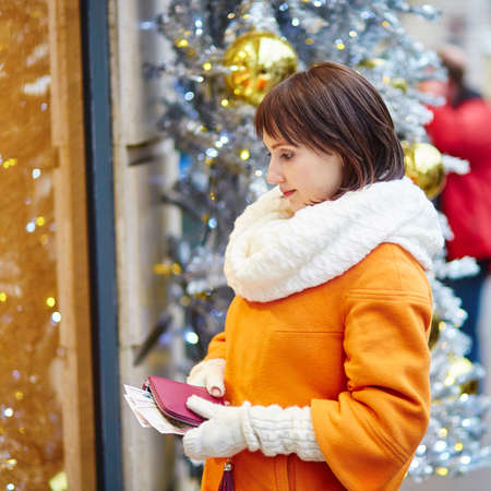 christmas lights display: Worried young woman holding purse with Russian roubles in shopping mall decorated for Christmas, financial crisis in Russia concept Stock Photo