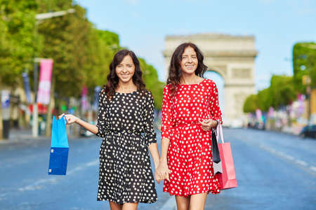 france: Happy twin sisters doing shopping on holidays in France, walking with shopping bags in front of Arc de Triomphe on Champs-Elysees, Paris, France