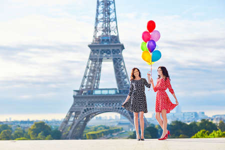 tour eiffel: Beautiful twin sisters in red and black polka dot dresses with huge bunch of colorful balloons in front of the Eiffel tower in Paris, France
