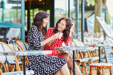 family and friends: Beautiful twin sisters drinking coffee in a cozy outdoor cafe in Paris, France. Happy smiling girls enjoy their vacation in Europe