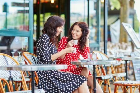 Beautiful twin sisters drinking coffee in a cozy outdoor cafe in Paris, France. Happy smiling girls enjoy their vacation in Europe