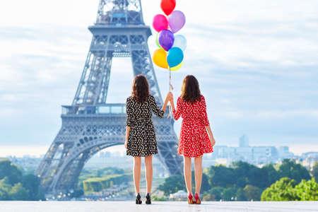 Mooie tweelingzusters in rood en zwart polka dot jurken met grote bos van kleurrijke ballonnen in de voorkant van de Eiffeltoren in Parijs, Frankrijk