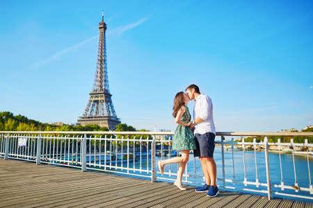 ロマンチックなカップル デートやキス、パリのセーヌ川の上の橋の上エッフェル塔を周辺します。