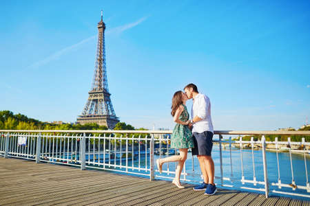 baiser amoureux: Jeune couple romantique ayant une date et en l'embrassant pr�s de la tour Eiffel sur un pont sur la Seine � Paris, France