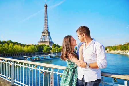 luna de miel: Pareja romántica joven que tiene una fecha cerca de la torre Eiffel en un puente sobre el Sena en París, Francia Foto de archivo