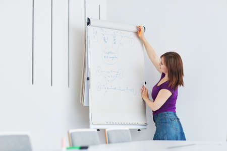 paper board: Pretty young student or business woman writing on a paper board during a class or business meeting