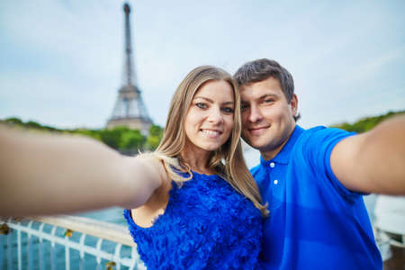 la tour eiffel: Beautiful young dating couple in Paris making funny selfie near the Eiffel tower