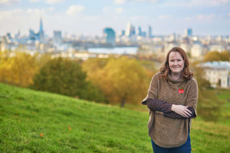 canary wharf: Girl wearing red remembrance poppy in Greenwich, London, UK, Canary Wharf in the background Stock Photo