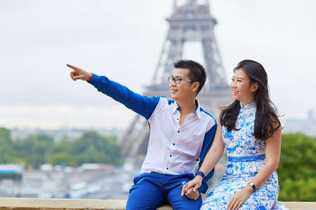 asian family: Young romantic Asian couple on Trocadero view point near the Eiffel tower in Paris, France