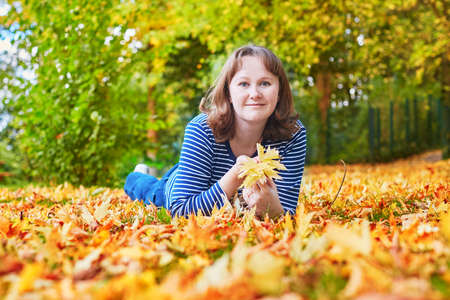 jardin de luxembourg: Cheerful young girl lying on the ground in fallen leaves on a bright autumn day