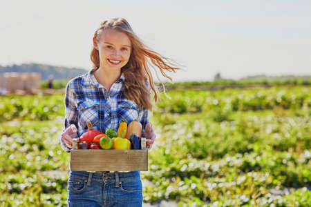 Happy young woman holding wooden crate with fresh organic vegetables from farm