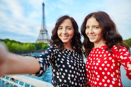 girl in red dress: Beautiful twin sisters taking selfie in front of Eiffel Tower while traveling in Paris, France. Happy smiling girls enjoy their vacation in Europe