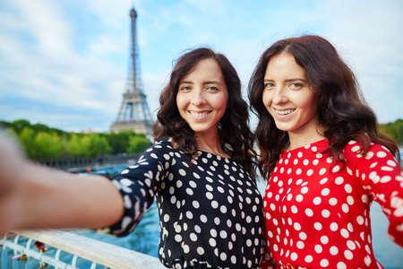 ni�as gemelas: Hermanas gemelas hermosas que toman selfie delante de la Torre Eiffel durante un viaje a Par�s, Francia. Ni�as sonrientes felices disfrutan de sus vacaciones en Europa Foto de archivo