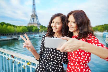 identical: Beautiful twin sisters taking selfie in front of Eiffel Tower while traveling in Paris, France. Happy smiling girls enjoy their vacation in Europe