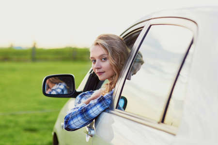 driver: Beautiful young driver looking out of the car window Stock Photo