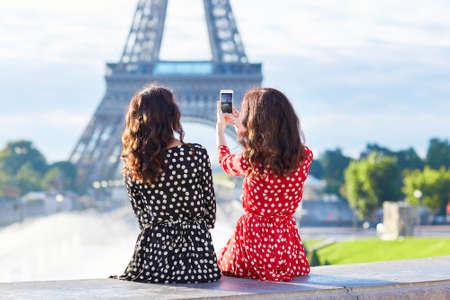 estilo urbano: hermanas gemelas hermosas fotografiando la Torre Eiffel durante el viaje en Par�s, Francia