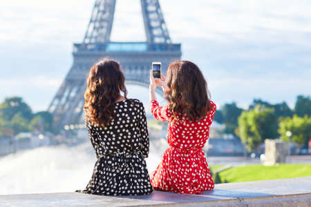 Beautiful twin sisters photographing the Eiffel Tower while traveling in Paris, France