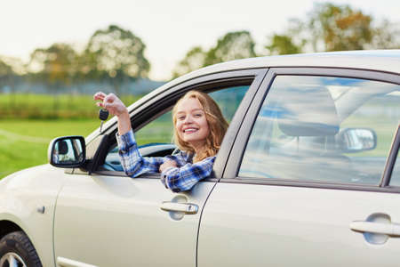 looking out: Beautiful young driver looking out of the car window holding a key