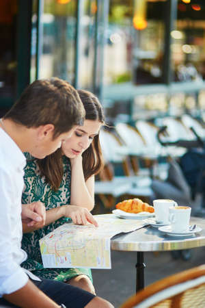 itinerary: Young romantic couple drinking coffee, eating traditional French croissants and planning their itinerary using map in a cozy outdoor cafe in Paris, France