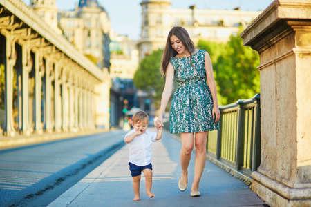 pies descalzos: Hermosa joven madre con su pequeño hijo adorable en el puente de Bir Hakeim en París, Francia