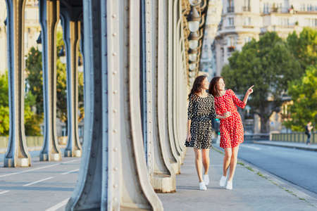 bir: Beautiful twin sisters in red and black polka dot dresses on the Bir Hakeim bridge in Paris, France