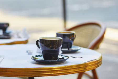 outdoor cafe: Coffee cups in an outdoor Parisian cafe Stock Photo