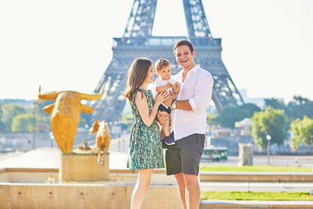 trocadero: Happy family of three standing in front of the Eiffel tower and enjoying their vacation in Paris, France